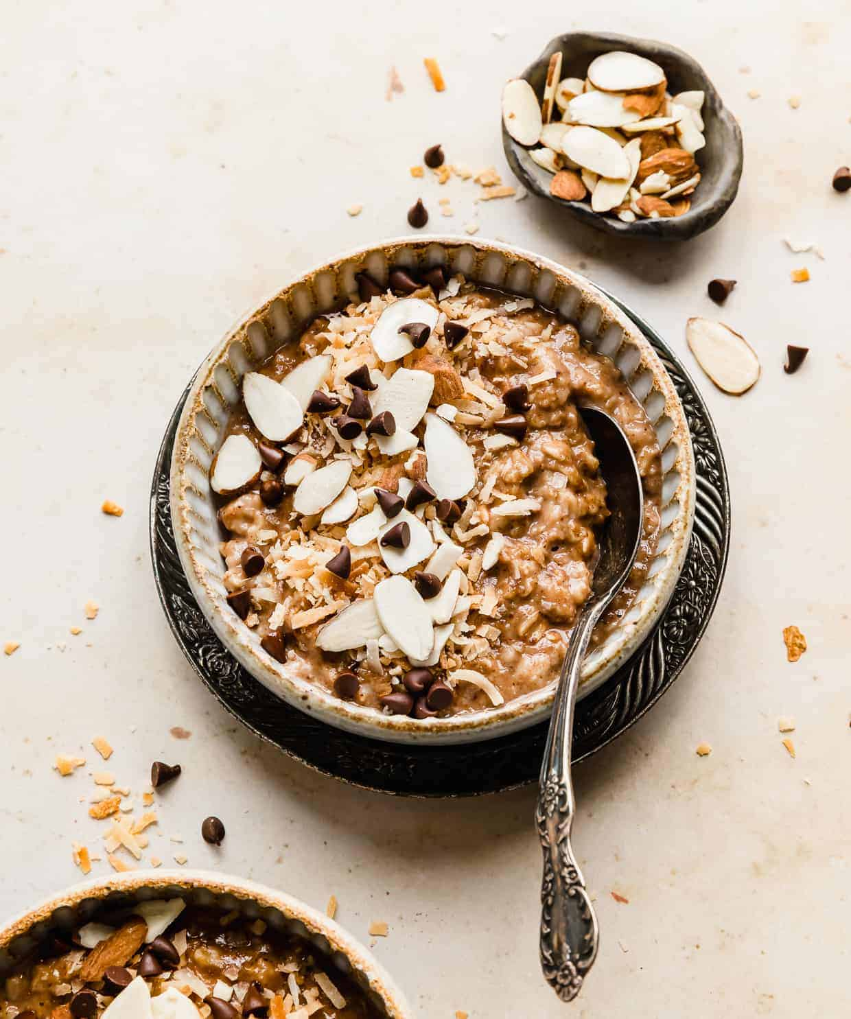 A bowl of almond joy oatmeal topped with sliced almonds and choc chips.
