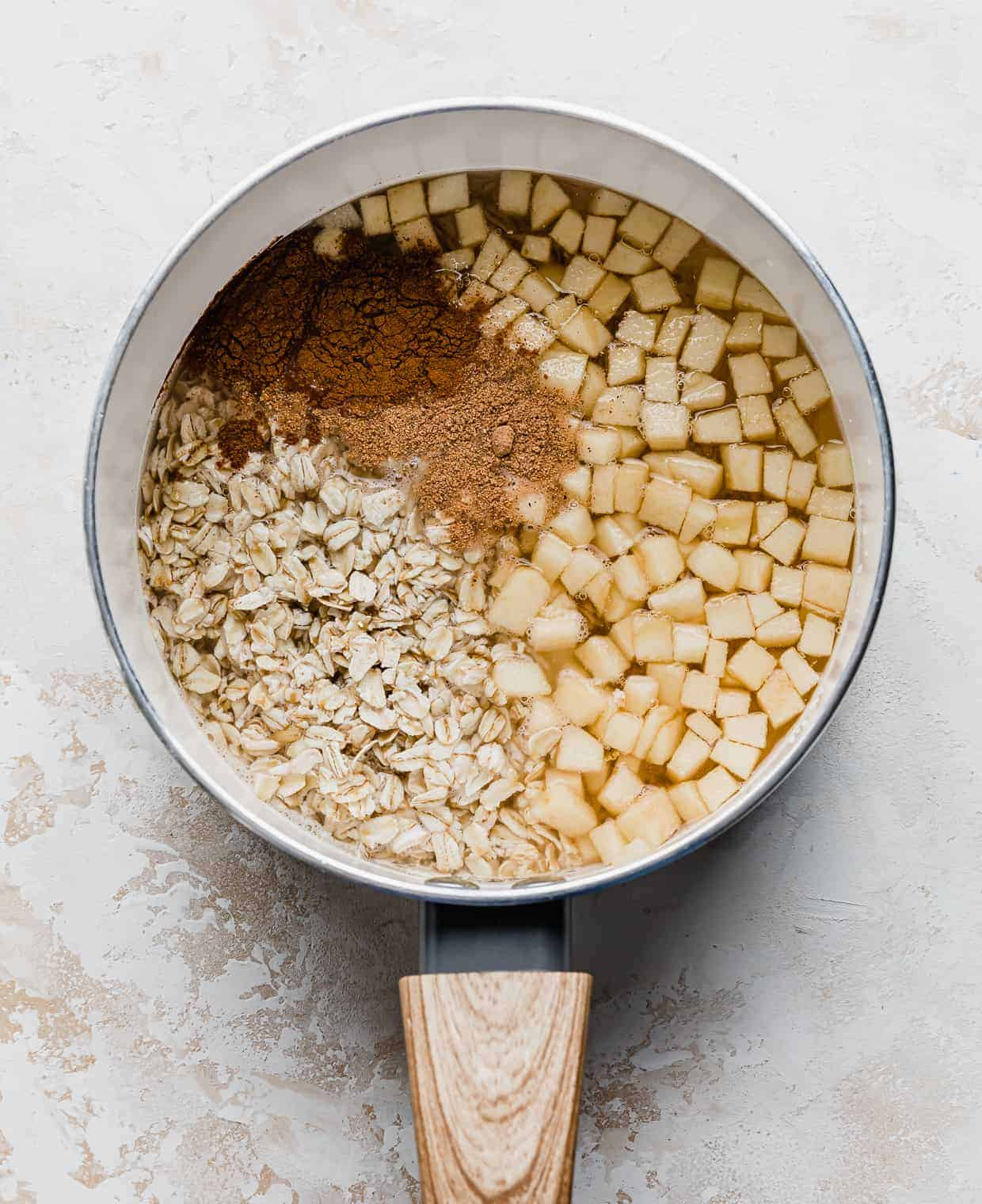 A saucepan with diced apples, water, oats, and cinnamon.
