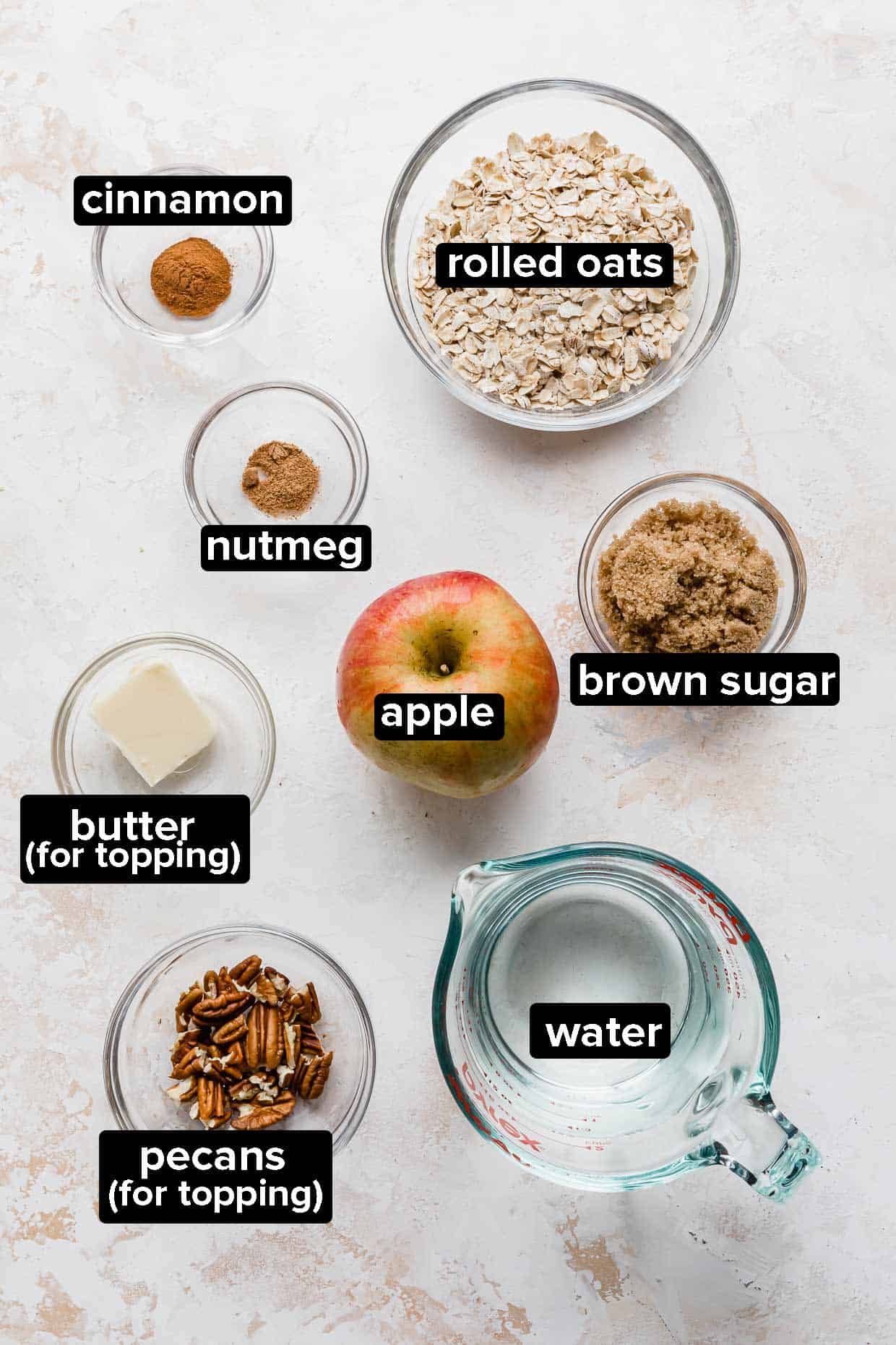 Ingredients used to make apple cinnamon oatmeal on a textured white background.