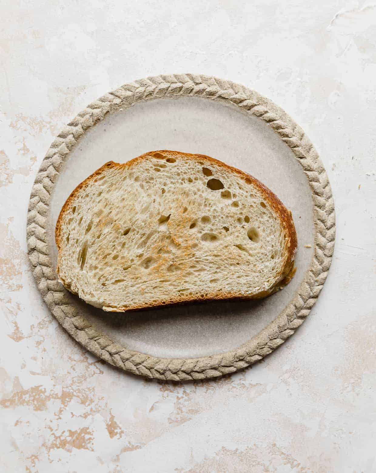 Slice of toasted French bread on a tan plate.