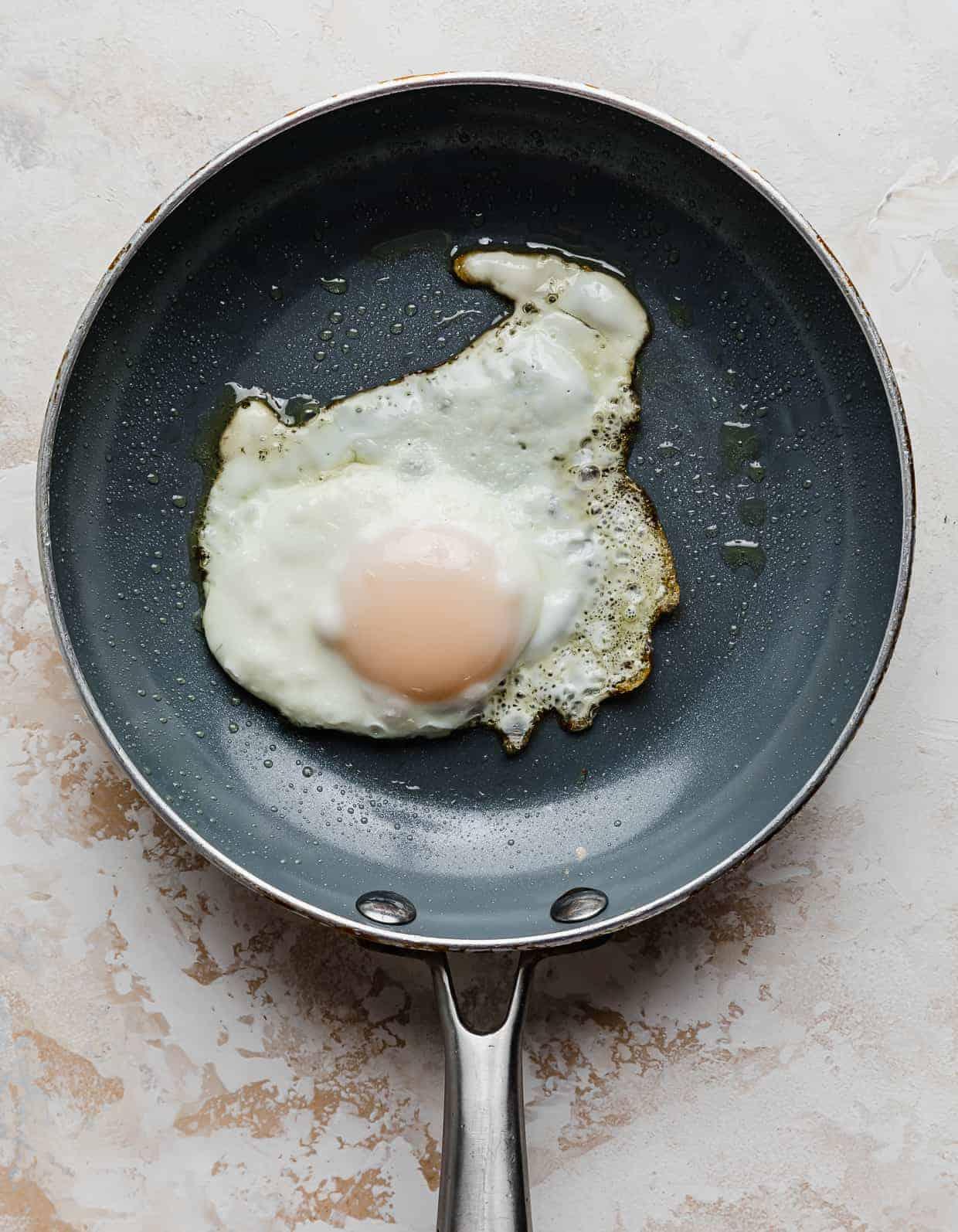 A sunny side up egg on a gray skillet.