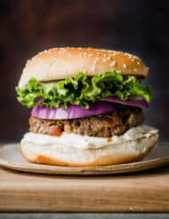 A bacon burger on a cutting board with green lettuce and purple onion on the burger.