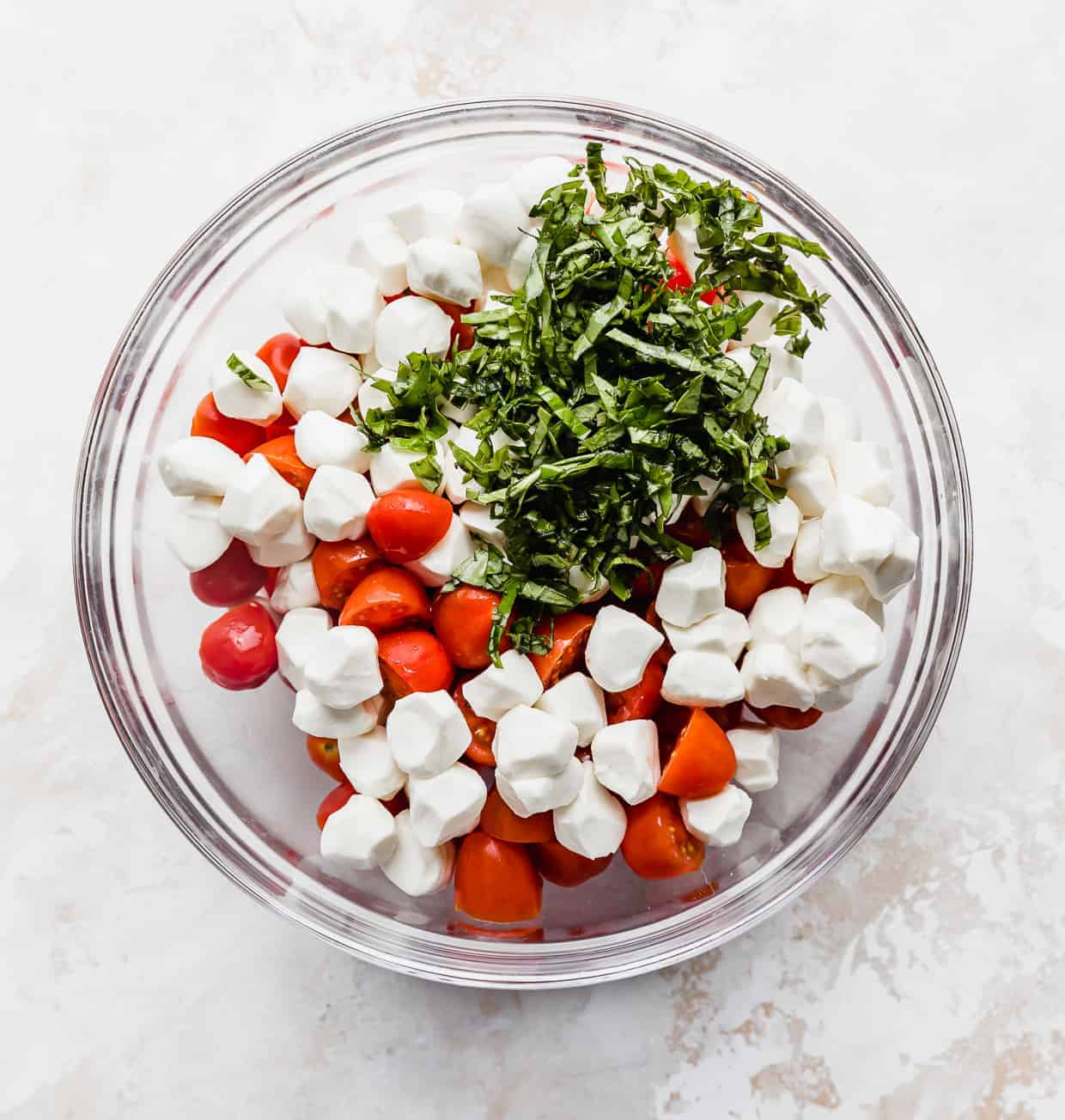A glass bowl with sliced cherry tomatoes, chopped basil, and mozzarella balls.