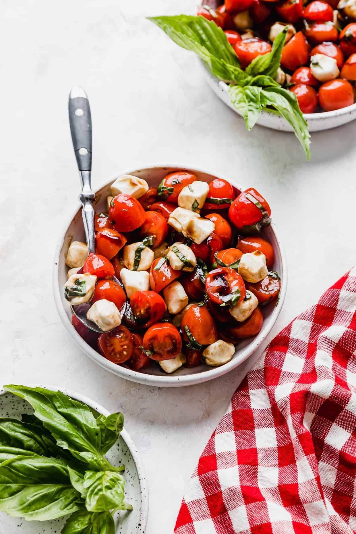 A white bowl with Cherry Tomato Caprese Salad in it, on a white background with fresh basil leaves in the foreground.