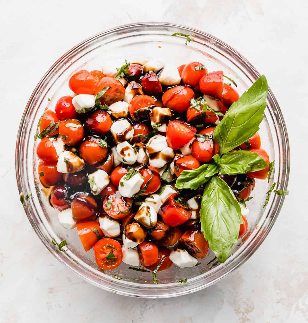 A cherry tomato caprese salad mixed with fresh mozzarella balls, fresh basil and a sprig of fresh basil on top.