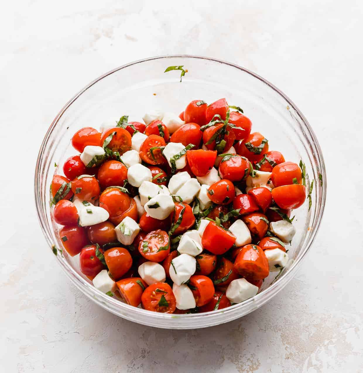 A glass bowl full of red grape tomatoes tossed with mozzarella balls and chopped basil.