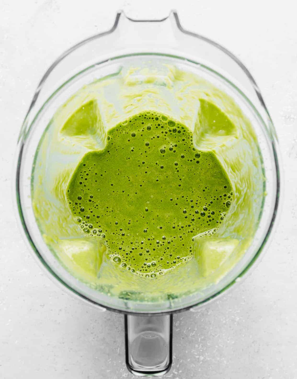 A blender with bright green celery smoothie in it.