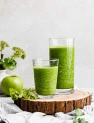 Two glasses full of dark green celery smoothie on a wooden round board.