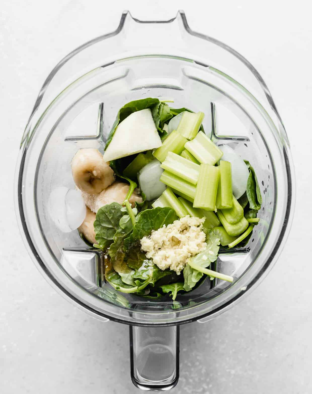Ingredients used to make a celery smoothie in a blender.
