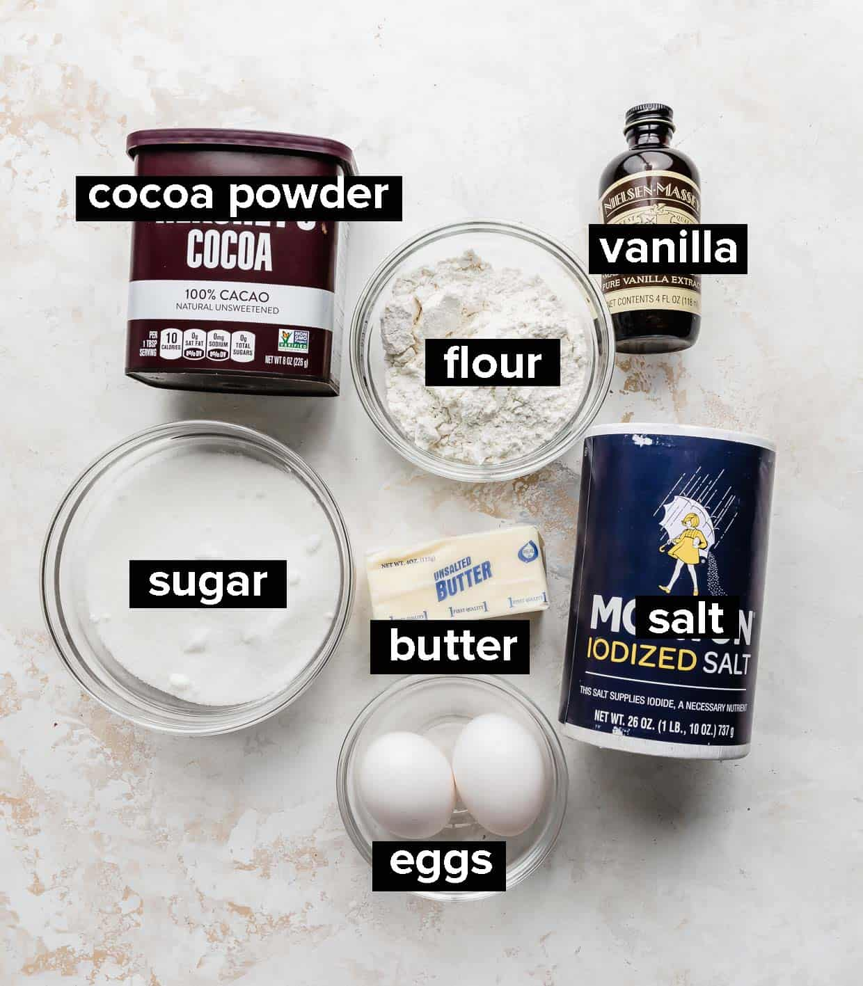Ingredients used to make lunch lady brownies set out on a white and cream textured background.