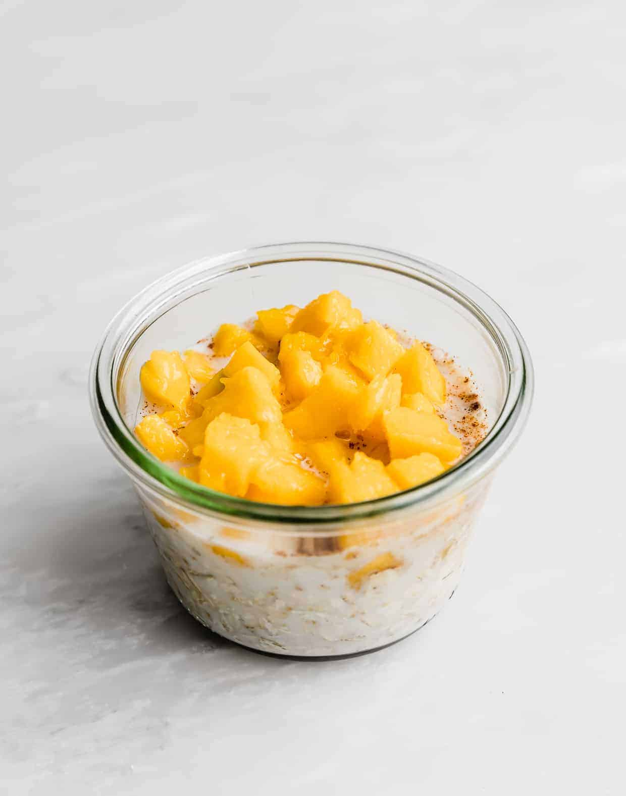 Diced mangos overtop of a milk and oat mixture in a glass jar.