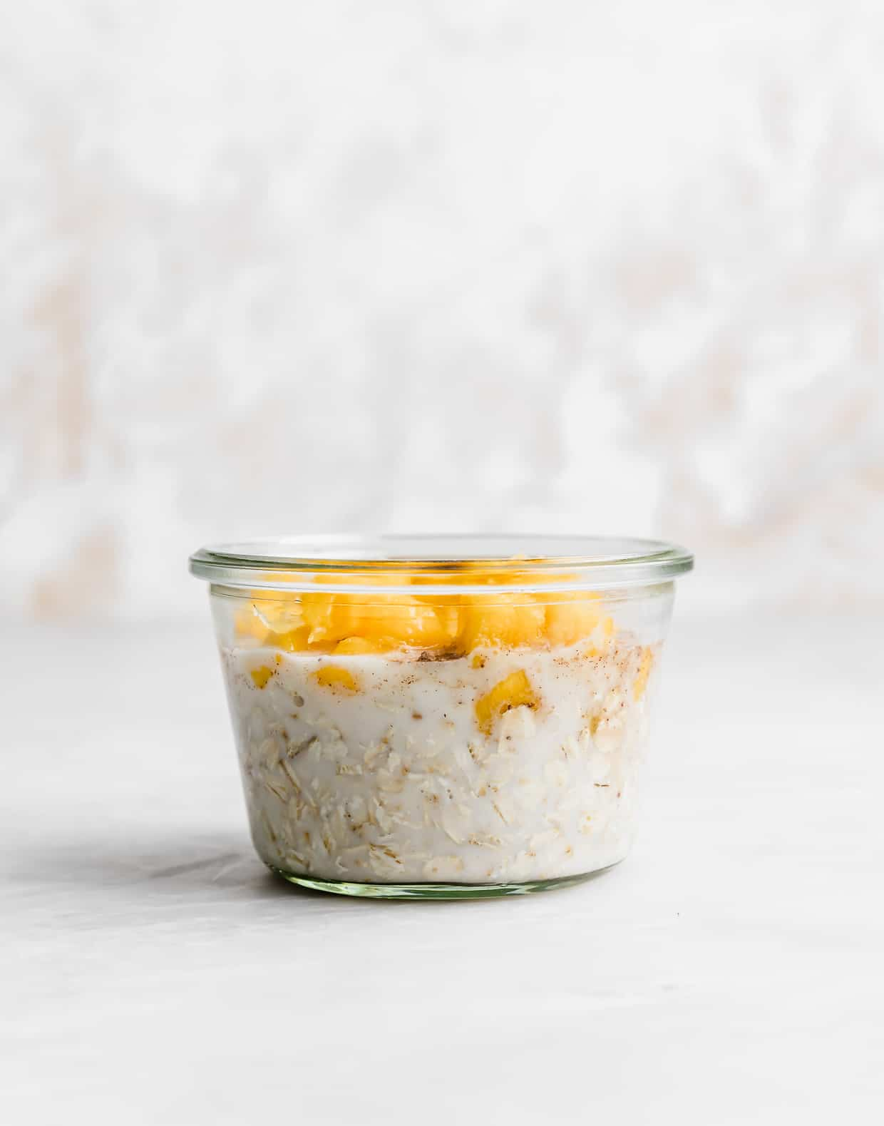 A glass jar with milk and oats on the bottom and diced mangos overtop.