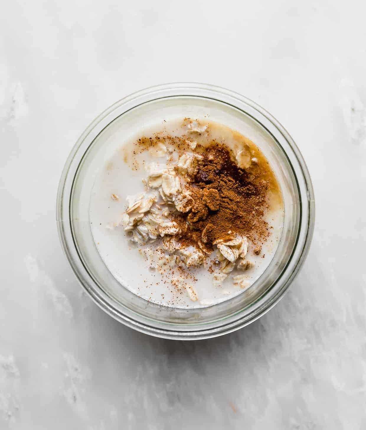 A glass jar full of rolled oats, milk, cinnamon, and nutmeg.