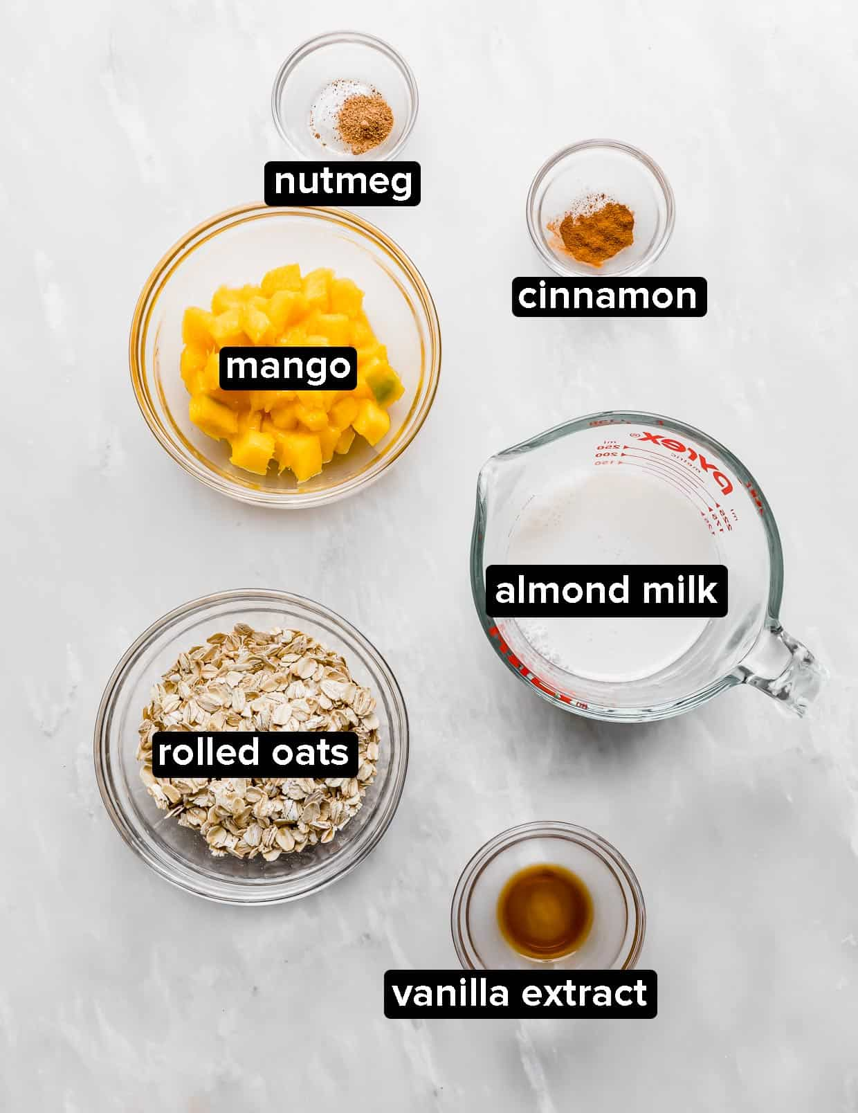 Ingredients used to make mango overnight oats, on a white background.