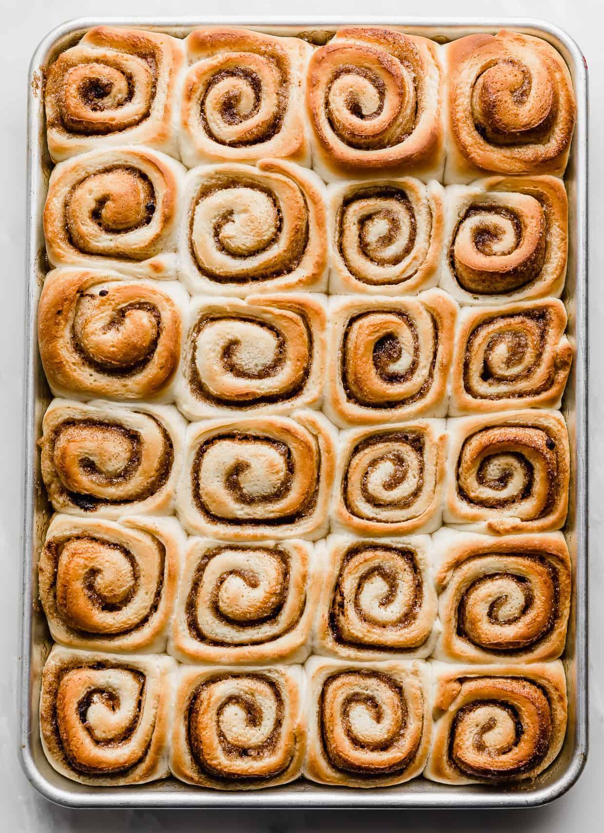 Golden brown baked mini cinnamon rolls on a baking sheet.
