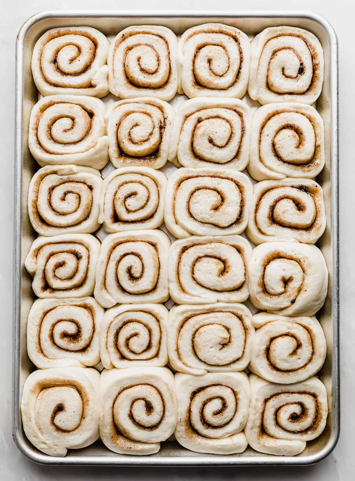 Mini cinnamon rolls on a baking sheet that have proofed and puffed up.