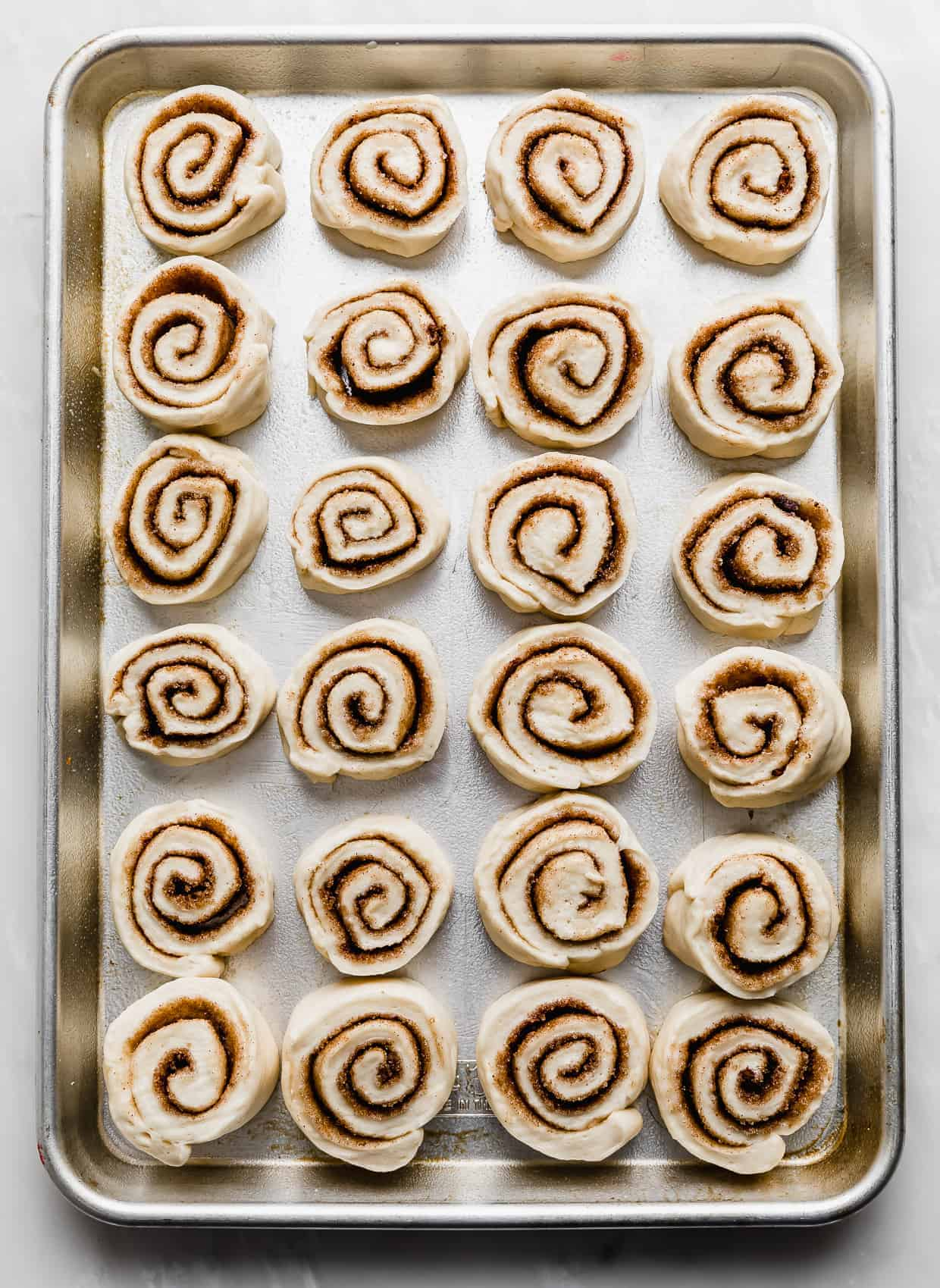A jelly roll pan with raw mini cinnamon rolls lined up on it, 4 across, 6 down.