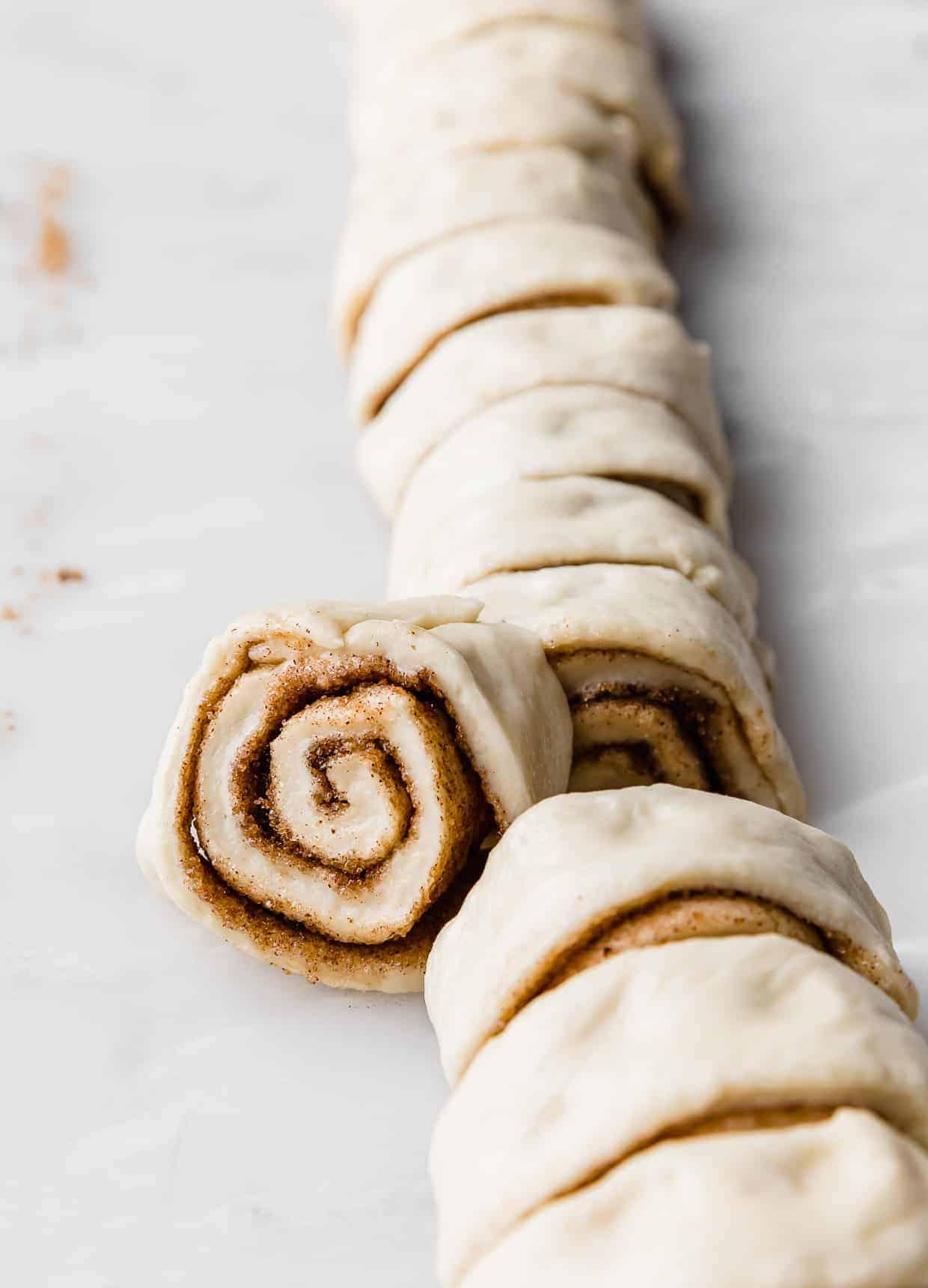 A raw mini cinnamon roll against a white background.
