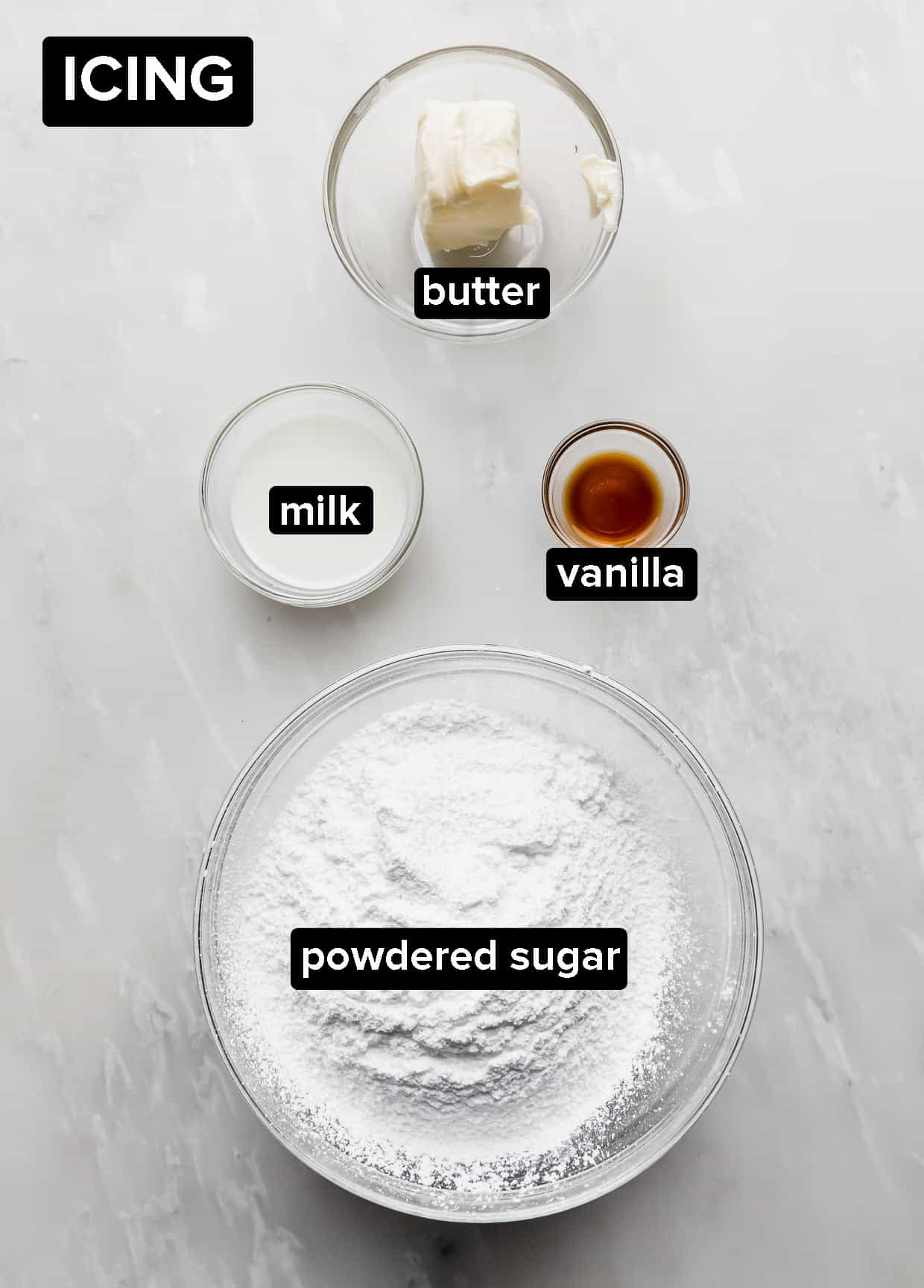 Ingredients used to make cinnamon roll icing on a white background.
