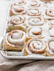 A metal spatula holding up a mini cinnamon roll in front of a baking sheet full of frosted cinnamon rolls.