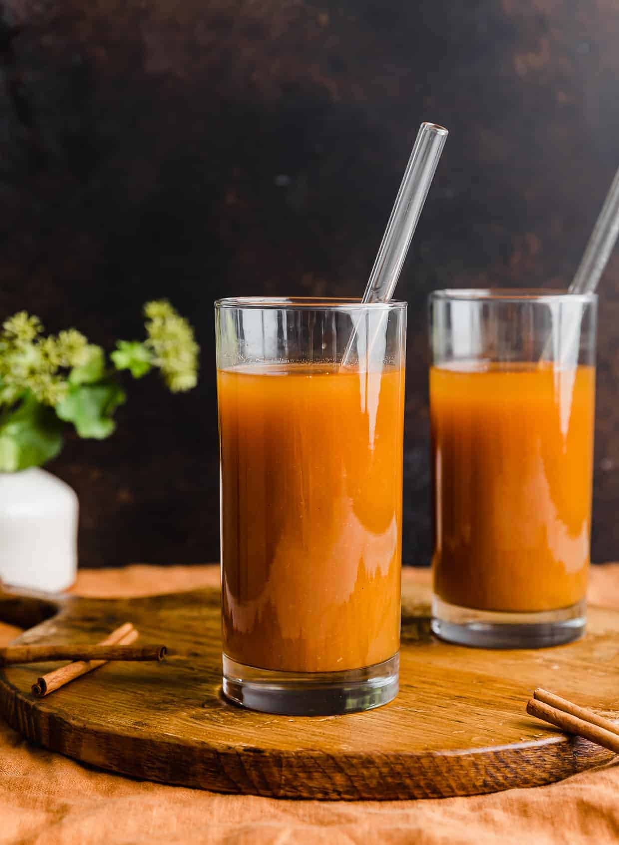 Two glasses with orange pumpkin juice in them against a brown background.