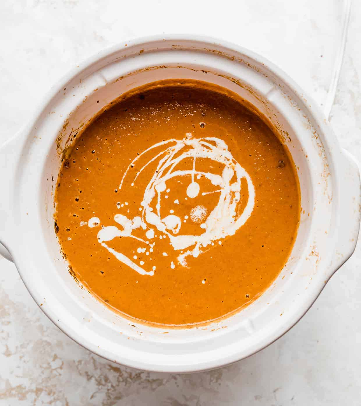 Creamy tomato basil soup in a white crock pot with cream drizzled overtop.