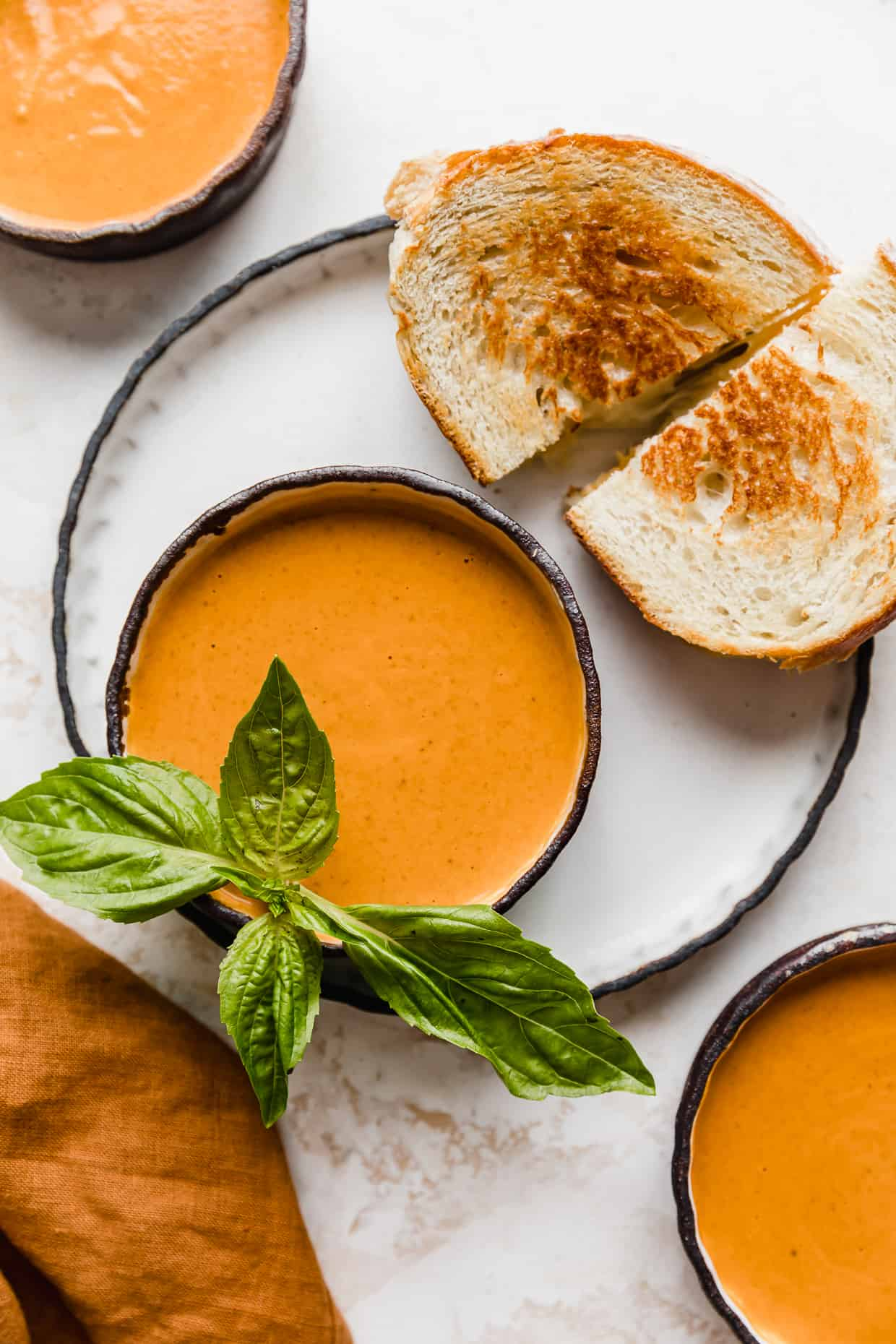 A bowl full of tomato basil soup with a grilled cheese next to the bowl.