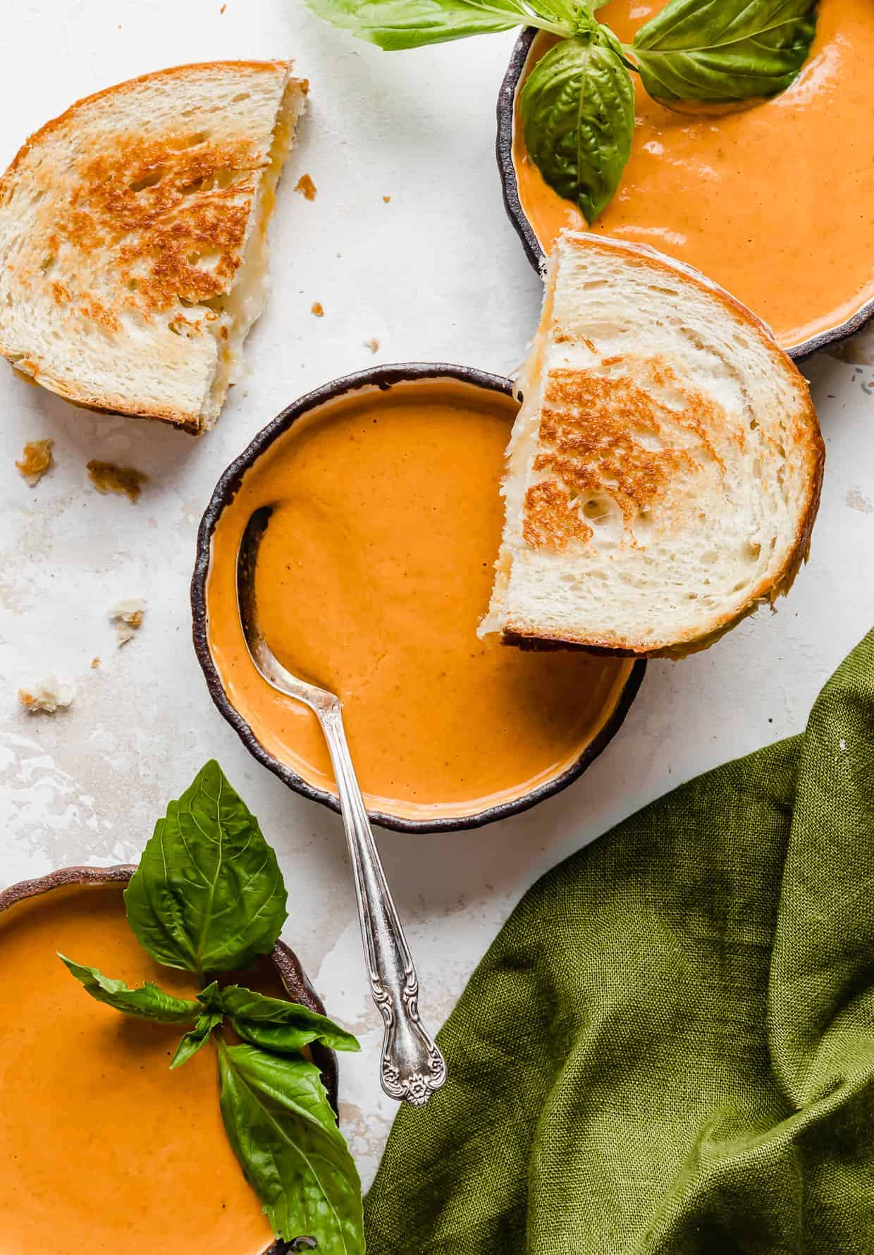 A black bowl full of creamy tomato basil soup on a white textured background.