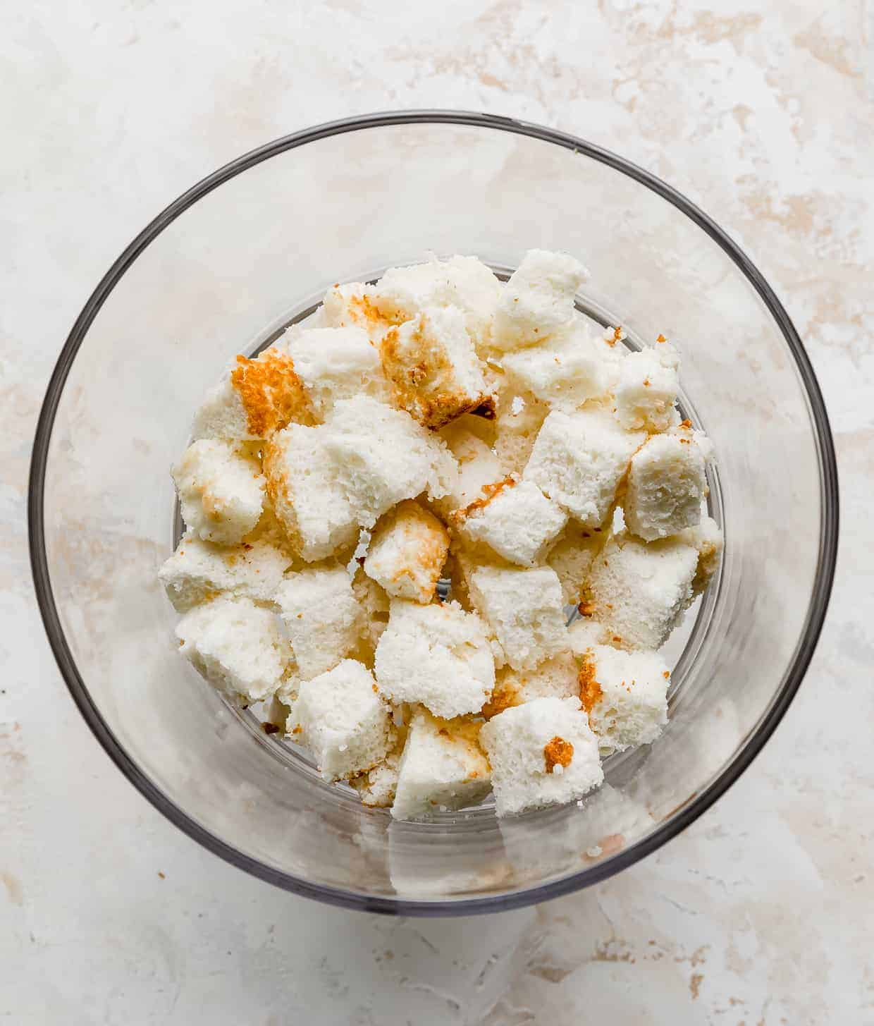 Cubed angel food cake in a trifle dish.