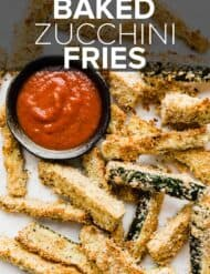 Baked zucchini fries on a white background with a small bowl of marinara to the side.