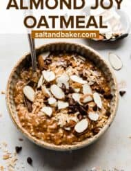 A bowl full of almond joy oatmeal that's topped with sliced almonds and chocolate chips.