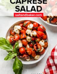 A bowl of cherry tomato caprese salad against a white background with a red checkered napkin in the foreground of the photo.