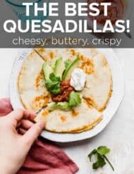 A cheese quesadilla topped with avocado, salsa, and sour cream.