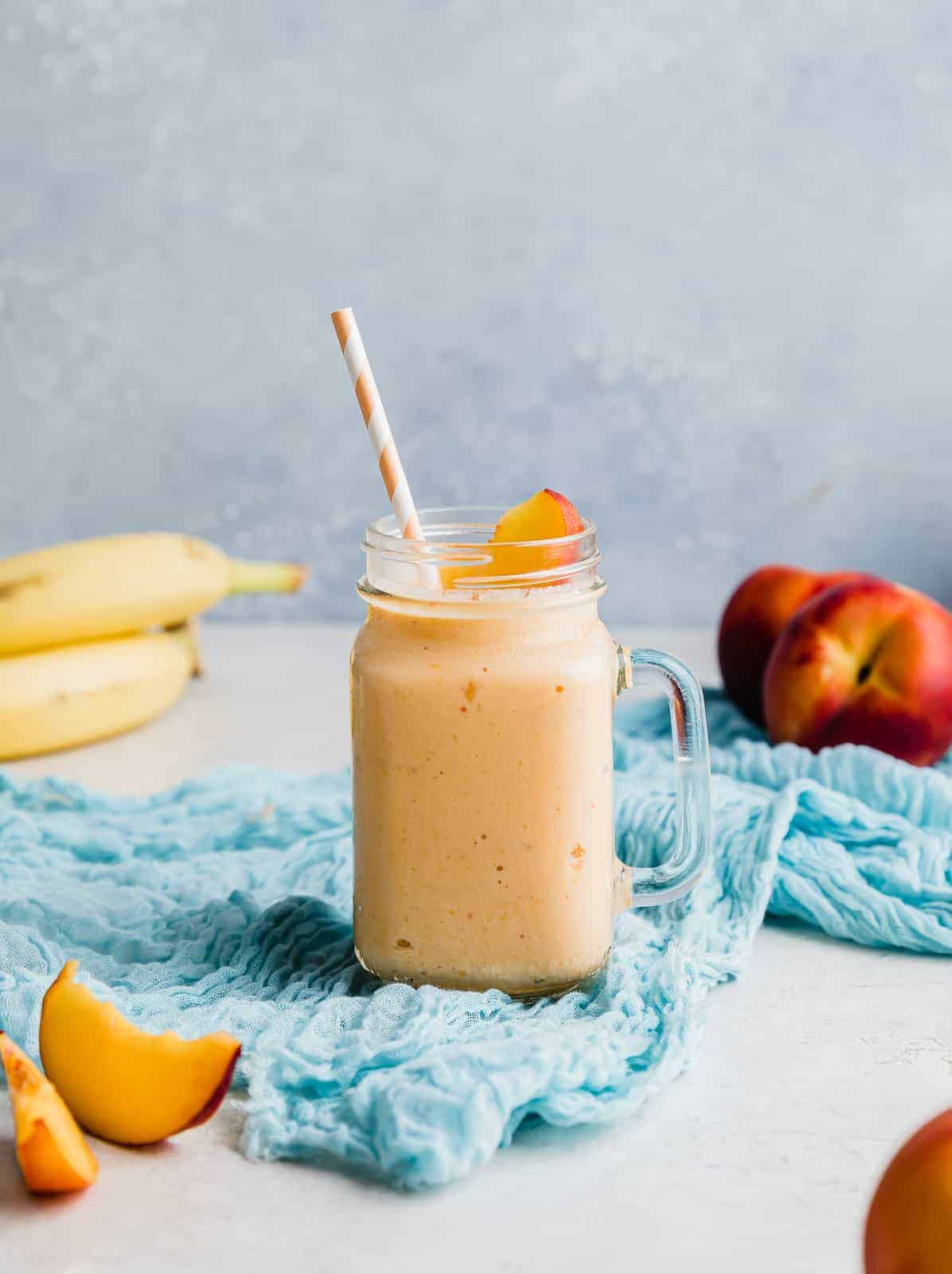 A banana peach smoothie in a glass cup with fresh peaches and bananas in the background.