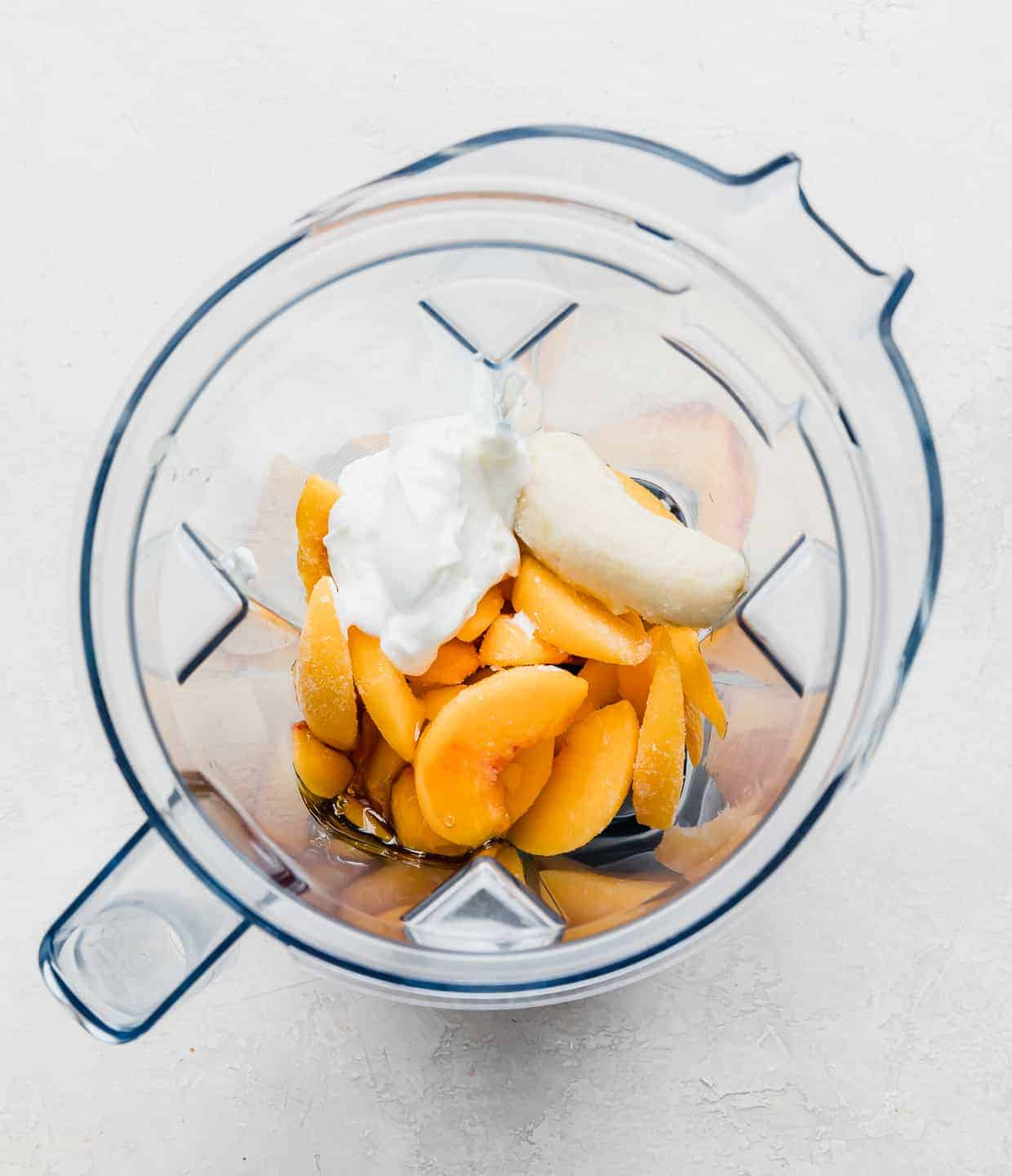 Overhead photo of a blender filled with frozen peach slices, yogurt, banana, milk, and honey.