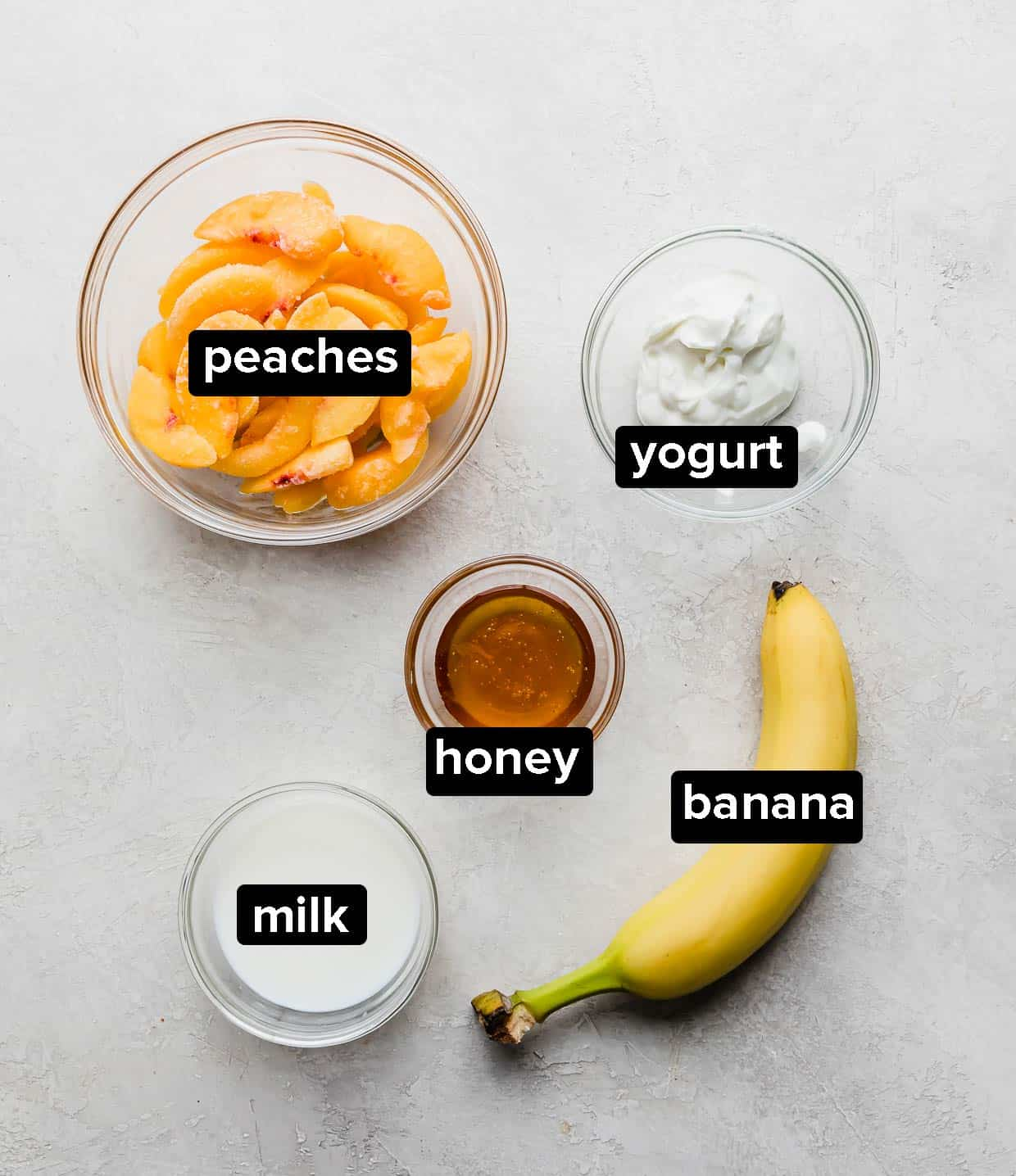 Ingredients used to make a banana peach smoothie on a gray background.