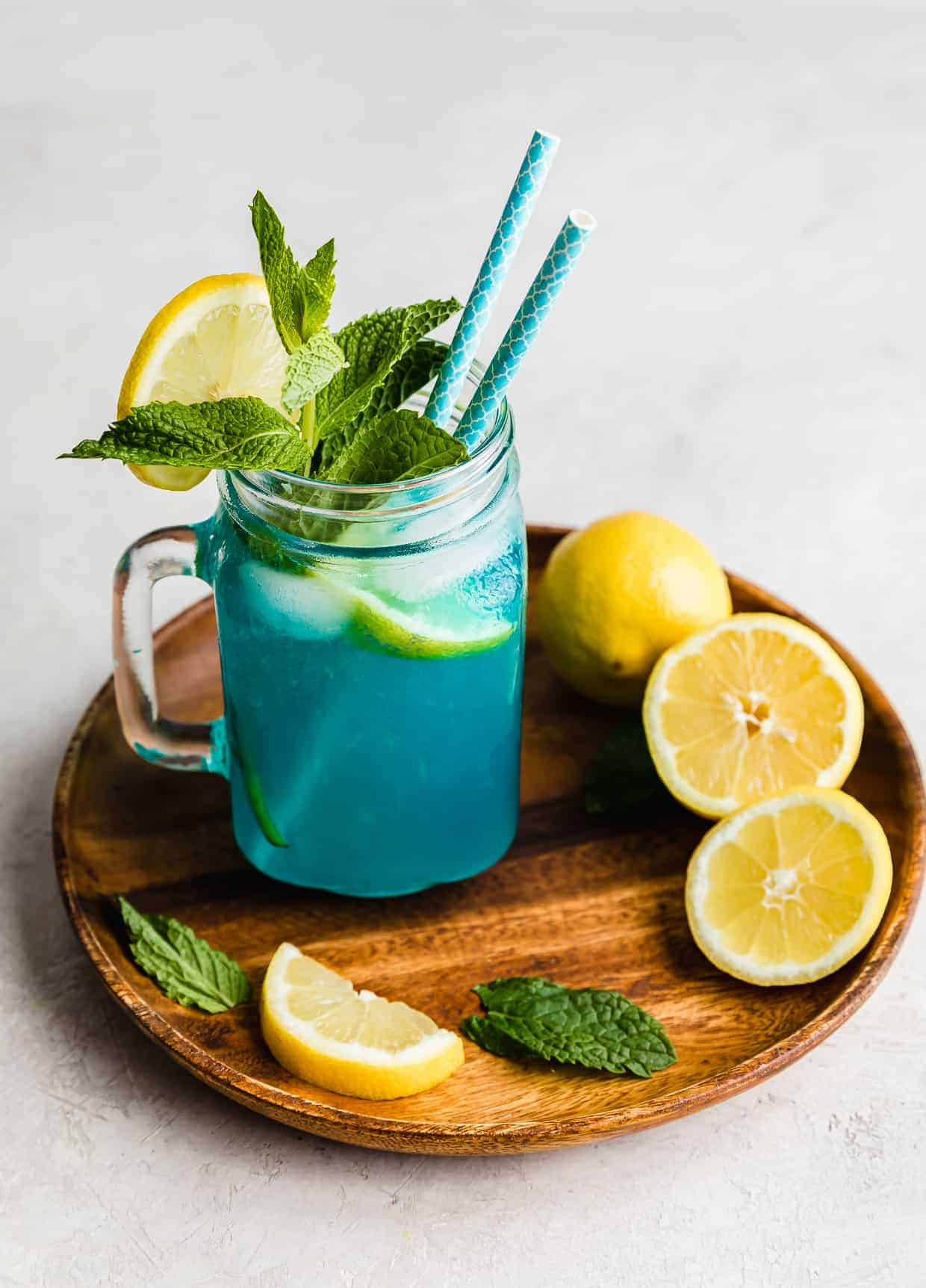 Blue Raspberry Lemonade in a glass cup on a brown plate surrounded by sliced lemons.