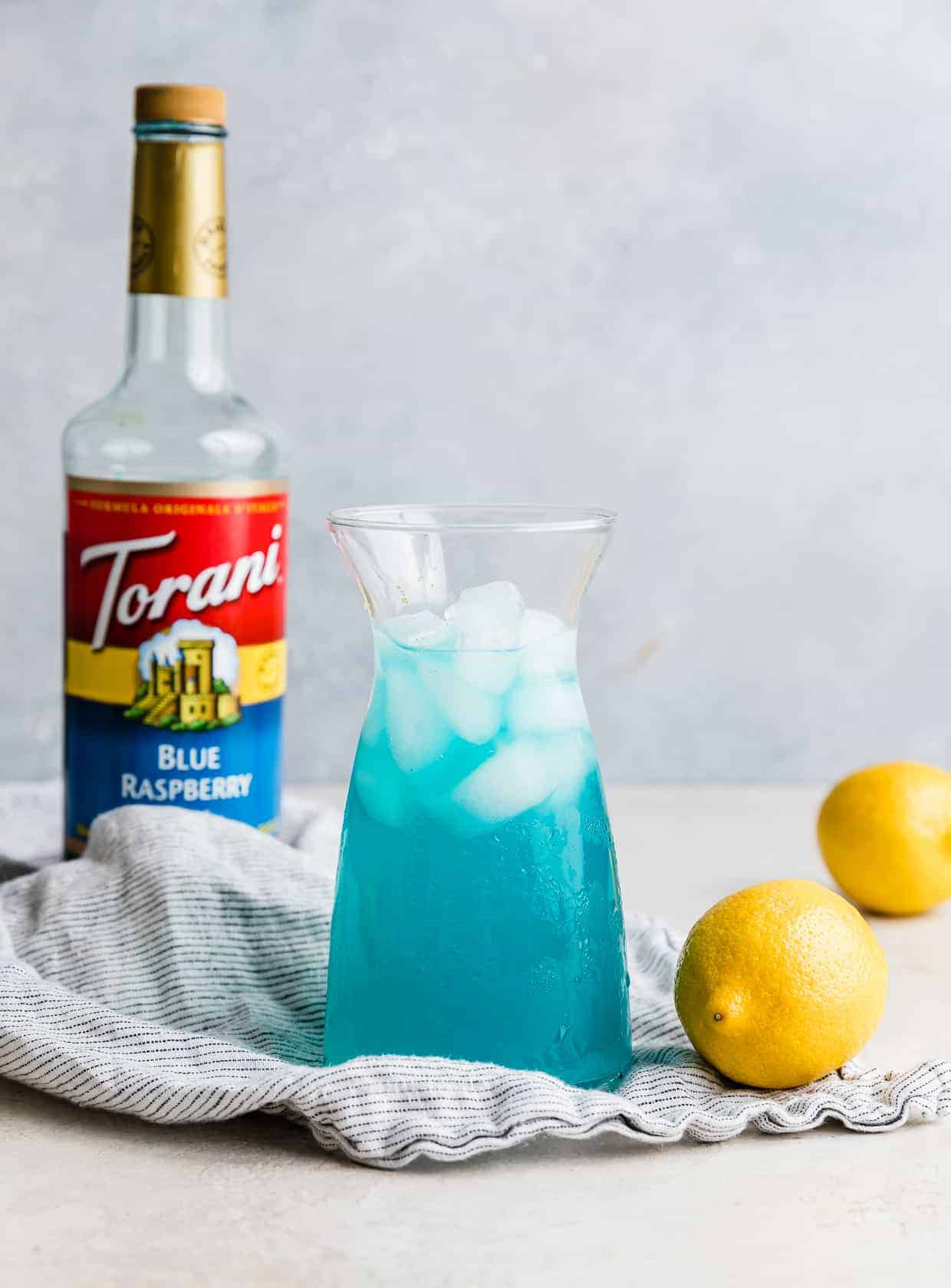 A jar of Blue Raspberry Lemonade against a gray background with a bottle of Torani blue syrup in the background.