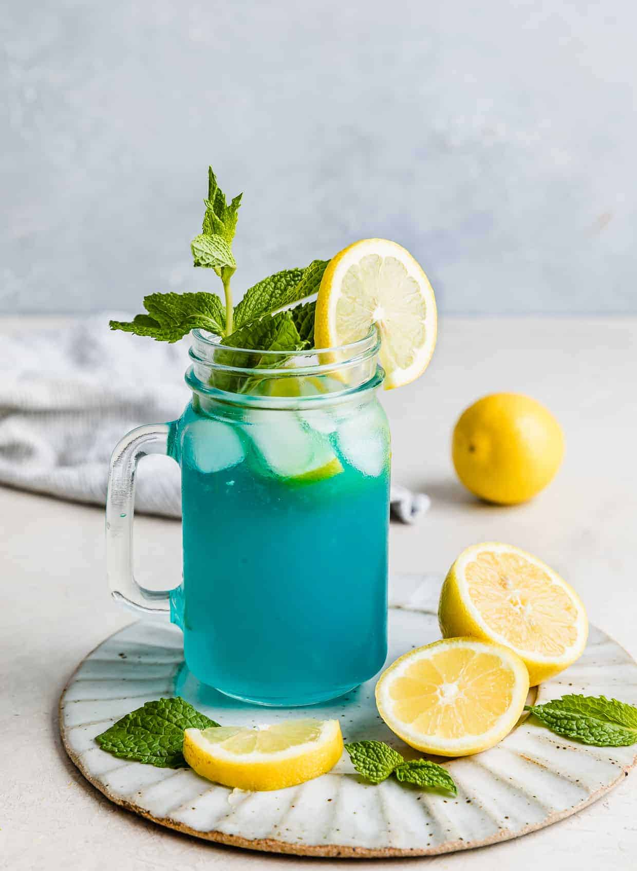 Blue Raspberry Lemonade in a glass jar garnished with a sprig of mint.