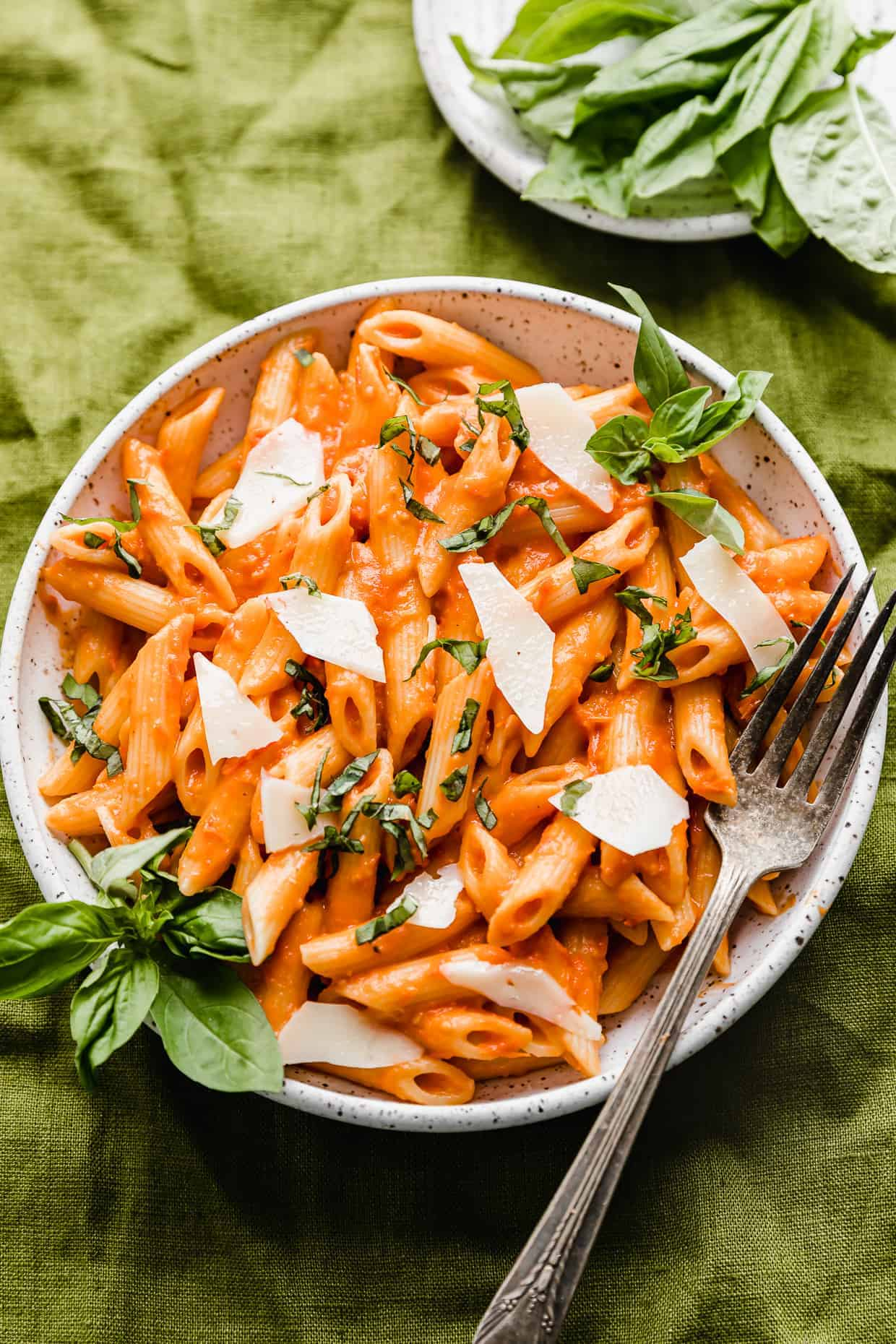 A white plate full of red Penne Pomodoro pasta topped with fresh basil.