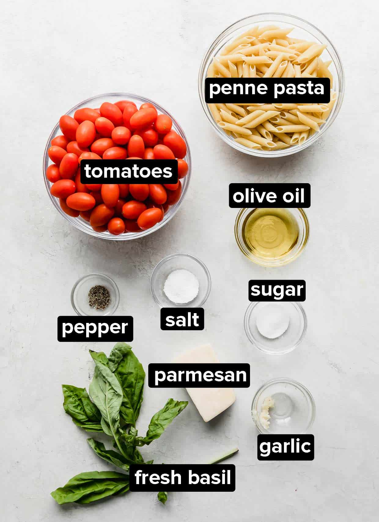 Ingredients used to make penne al Pomodoro on a white background.