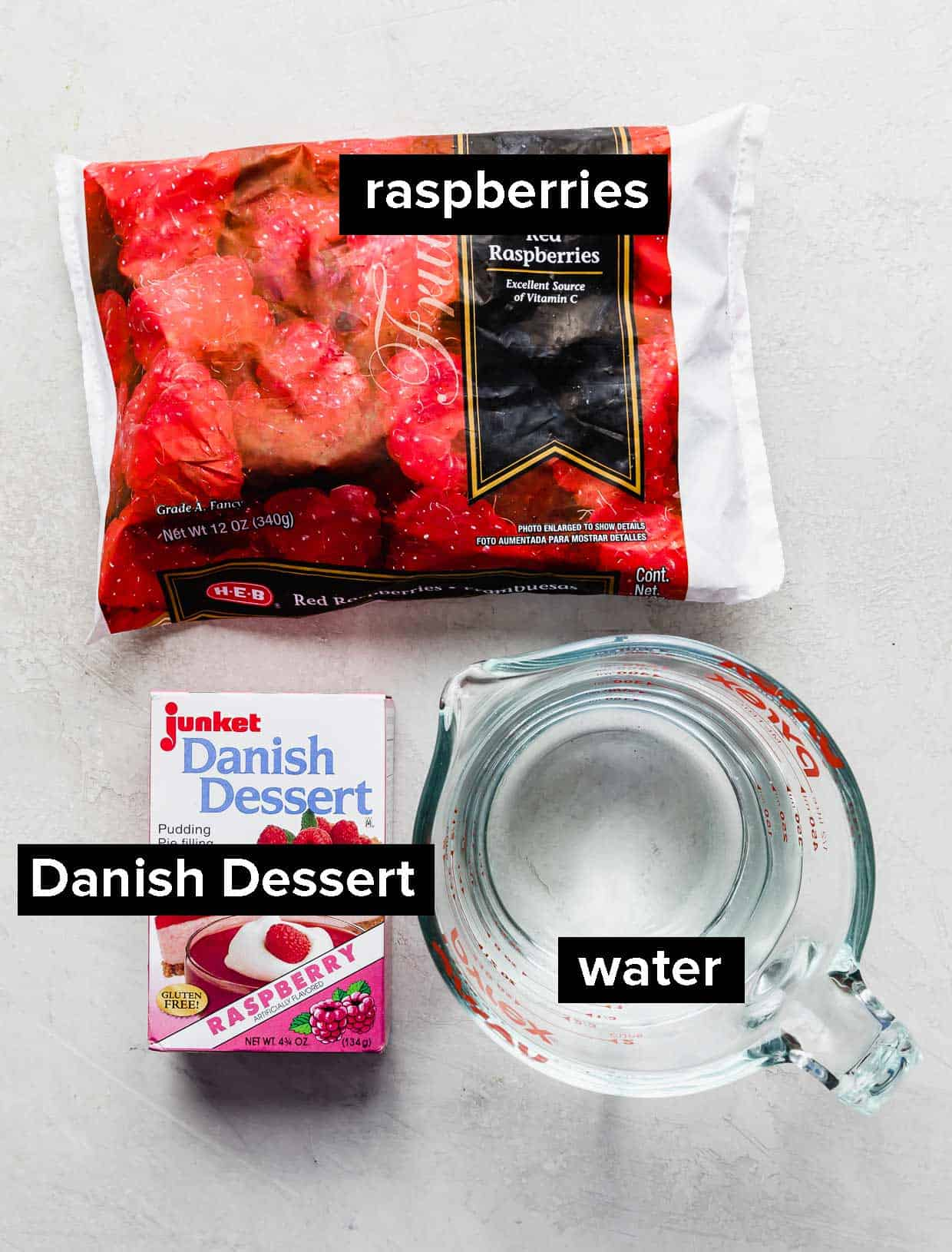 A bag of frozen raspberries, box of Danish Dessert, and water on a gray background.