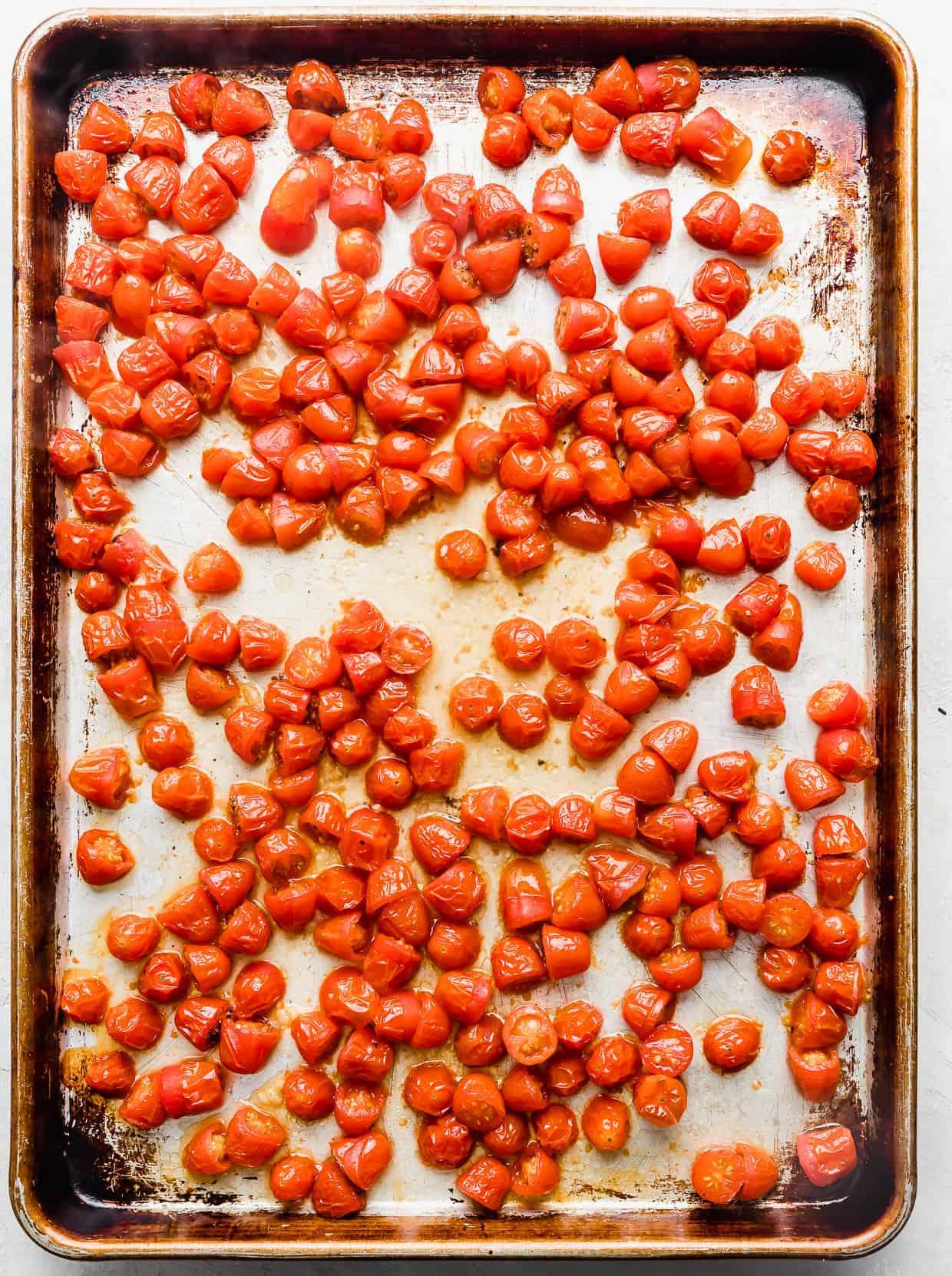 Shriveled roasted red tomatoes on a baking sheet.