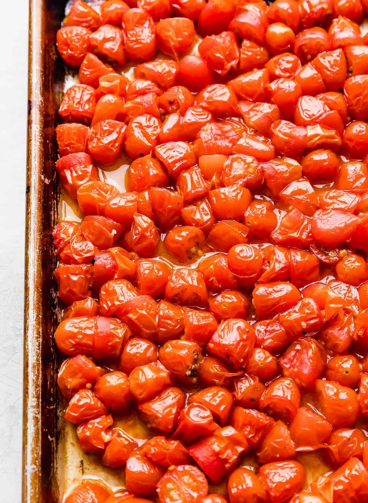 Roasted small red tomatoes cut in half, on a baking sheet.