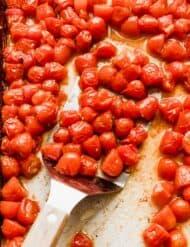 Roasted grape tomatoes on a baking sheet.