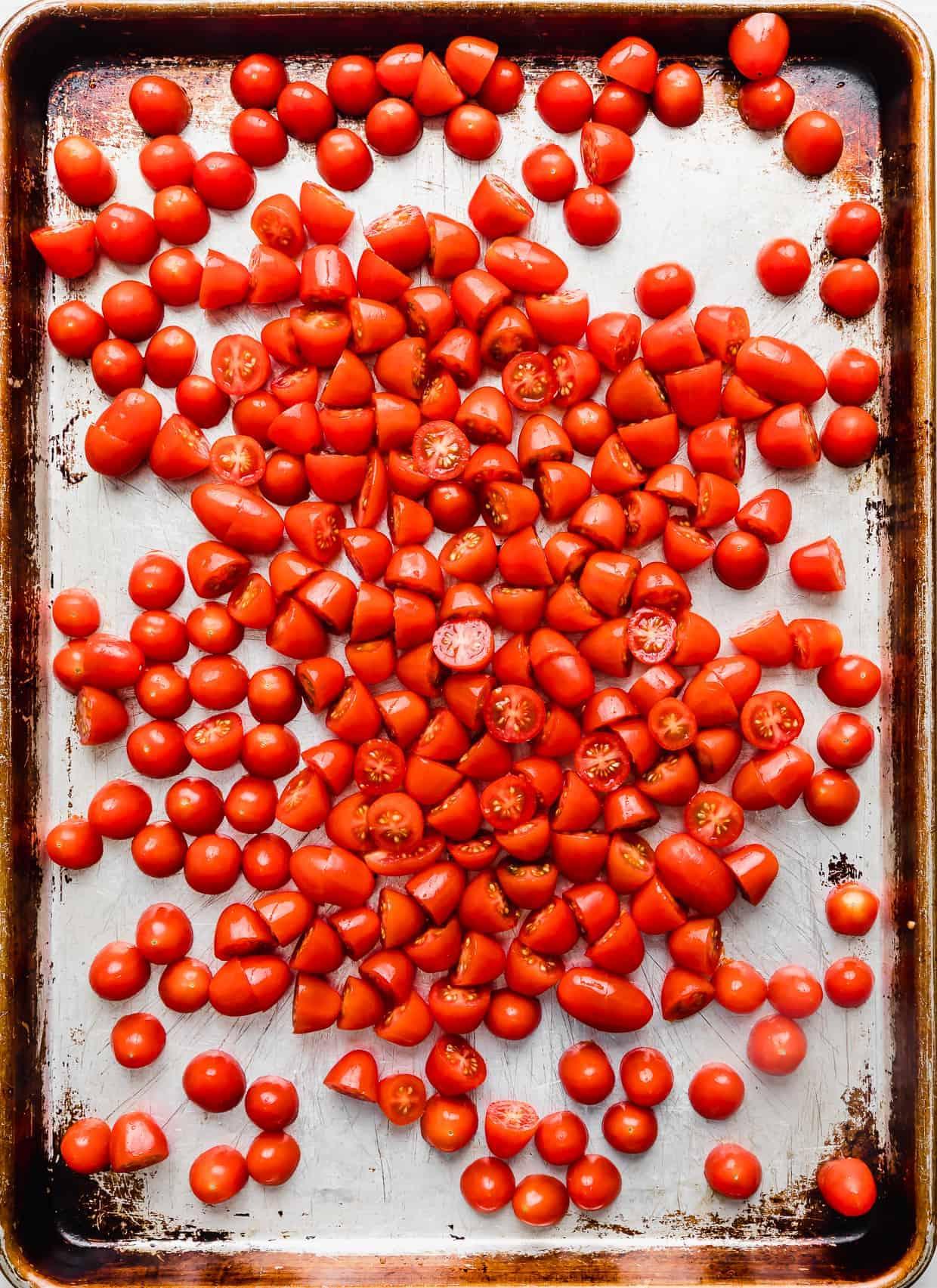 Grape tomatoes on a baking sheet.