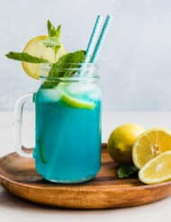 A jar of Blue Raspberry Lemonade on a brown plate, garnished with a sprig of fresh mint and lemon slice.