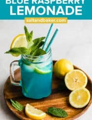 A glass jar with Blue Raspberry Lemonade in it and 2 blue straws.