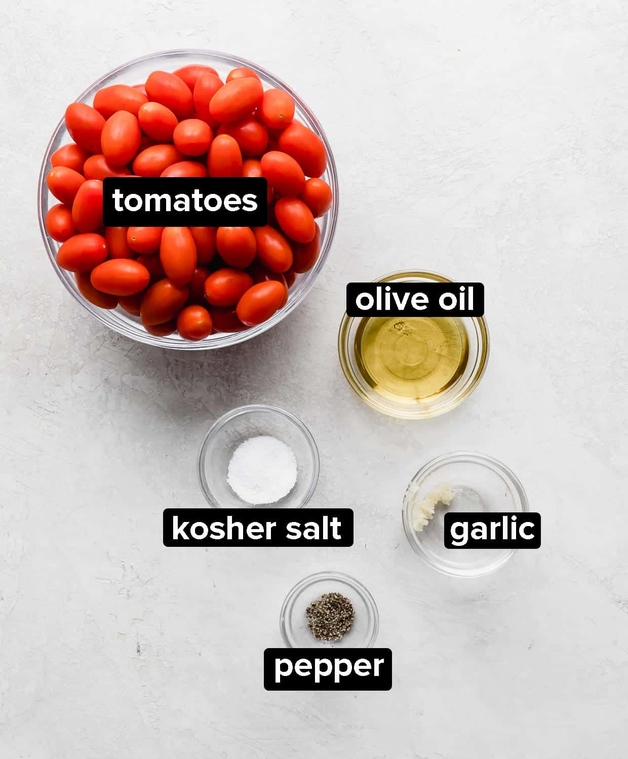 Ingredients used to make roasted tomatoes, on a gray background.