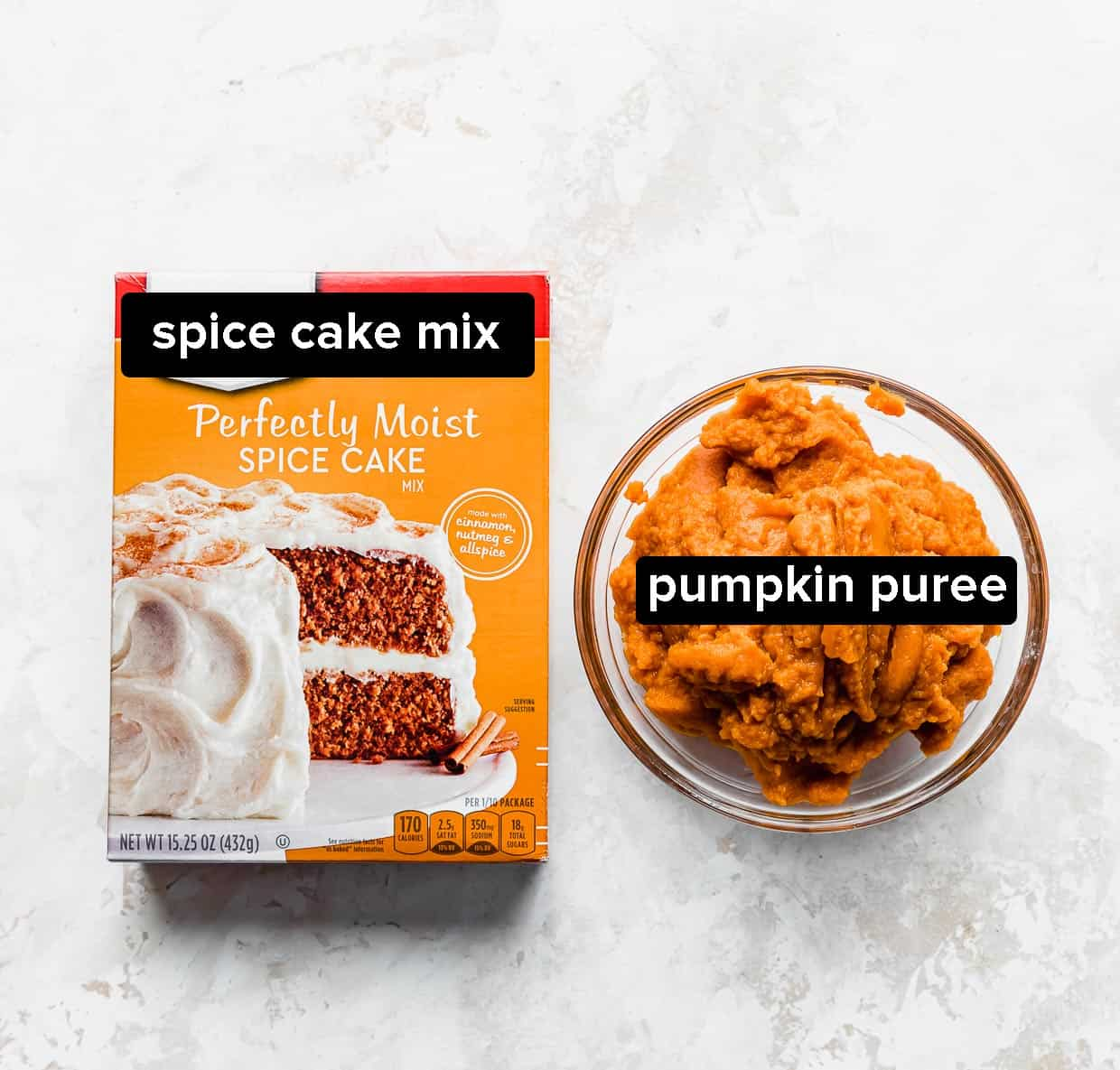 A box of spice cake mix and a bowl of pumpkin puree on a cream textured background.
